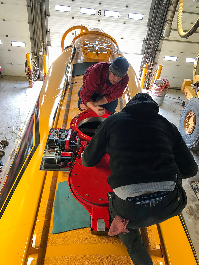 Two technicians working on the installation of the hatch